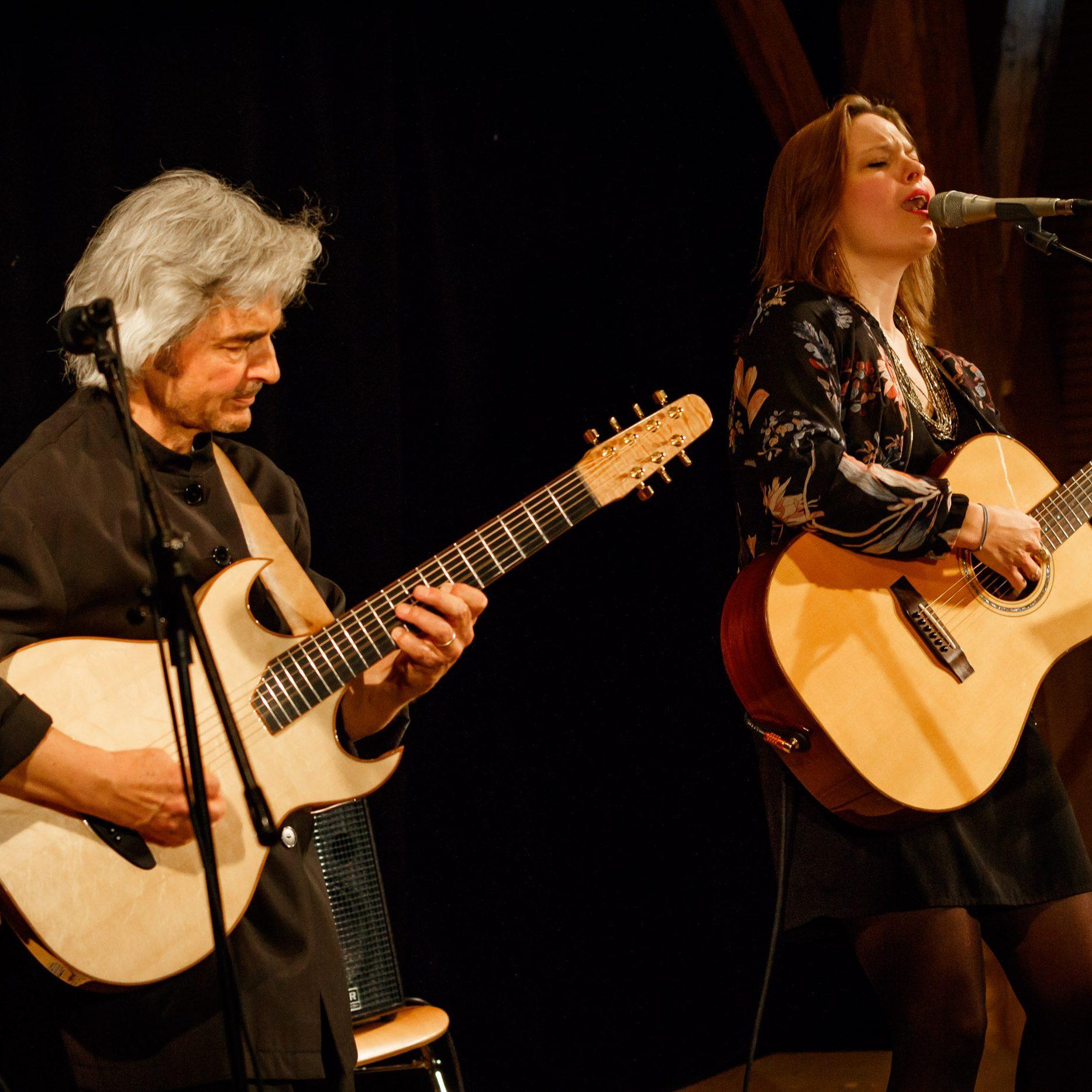 Amelie Haidt (Vocals, Guitar), und Wolfgang Netzer (6/7/12 string Guitars, Oud, Vocals) stehen auf der Bühne des Kulturvereins UNSER DORF.e.V im Pfarrstadel in Weßling am 21. April 2017